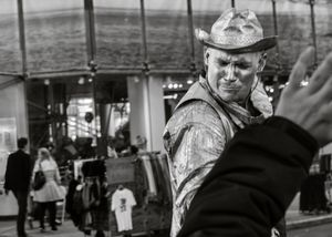 The Silver Cowboy: a living statue street performer stands frozen in time at the center of the world's great cities, and springs to life when tourists drop a dollar in his bucket.
