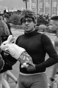 A teenager accompanied by his pet bunny rabbit, dressed for the occasion.