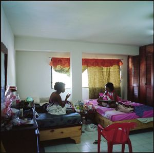 Sahomy, with her best friend and roommate in their apartment, checking over her earnings in the ledger she keeps