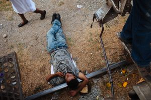A migrant sleeps over the railroad waiting for the train departure in Arriaga, Mexico. April 21, 2013.
