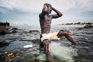 Kherou Ngor, a young wrestling champion, washes himself with milk at the shore of Ngor, Dakar, August 11, 2015. He performs this ritual in order to obtain the reinforcement of a ghost who lives in the stones at the shore.