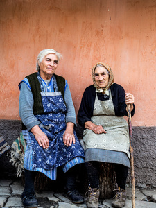 Anka's aunt & Grandmother sitting with terracotta wall, Saschiz 2015