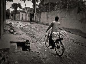 Bicyclist on a muddy road, Lazimpat, Kathmandu