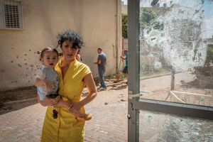 An Israeli women hold her baby and runs, moments after a rocket launched from the Gaza Strip hits a house in the  southern city of Sderot, Israel, 2014.