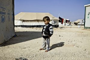A little boy next to his tent home. © Tom Verbruggen