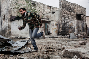 A FSA fighter running across the street while a sniper is shooting against him.