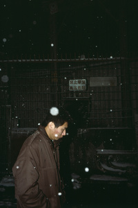 Man walks in snow in back streets. Christmas Day. Xi'an, China. 25 December 2006
