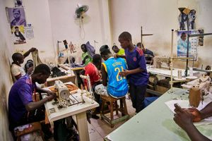 """September 26, 2018 - Young men work in your tailor's shop in the """"Centre Commercial de Touba"""" on Bou-Bous, the traditional Senegalese robes. The textile workers in this room all belong to the same Dahira. On the walls of the tailor's shop there are posters of the marabouts to which the workers commit themselves and pay their contributions."""