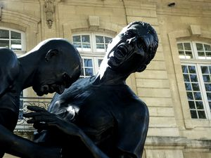 A huge black statue of a struggle between men that ended by a headbanging.