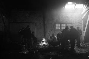 Migrants are gathering around a fire inside the train depot they are living in.