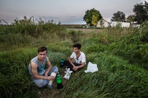 September 2016, Horgos, Serbia. Two Kurdish refugees from Syria are relaxing just outside a refugee camp at the Serbian Hungarian border, as here is not much to do in the very basic camp. They are waiting for months to get their asylum claim processed by Hungarian authorities, not knowing when it will be their turn.