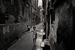A girl skipping in a narrow alley. Modon Shaha Lane, 2006. © Munem Wasif