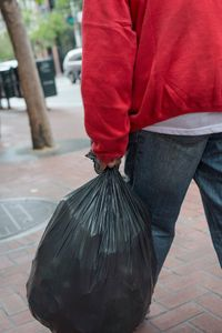 Man with Red Sweatshirt and Garbage Bag