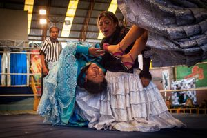 Juanita La Cariñosa and Simpática Sónia punish Jennifer Dos Caras, during a fight on the 12th October Sports Complex in El Alto.