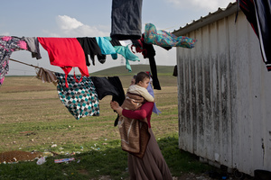 Ghazal hangs up the family laundry while holding her grandson, Mazal.The family of Yezidis, displaced from Sinjar, live next to an oil refinery in the Kurdish Region of Iraq. The young men run the refinery 24 hours a day with little to no safety equipment. 17/02/15, Tanjero, Iraq.