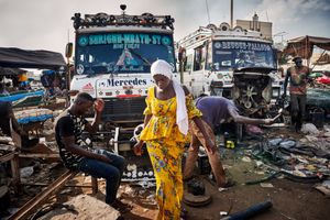 October 1, 2018 - A girl walks between workers who reassemble buses from used metal parts in an open-air garage in the centre of Dakar. With these buses, tenthousands of people will be transported to the Grand Magal in Touba at the end of the month. The marabouts are omnipresent in Senegal, stickers and inscriptions with their portraits are applied on the windows of almost all buses and taxis.