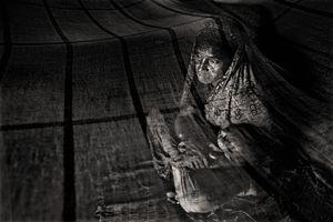 Sorifa Khatun (30) rocks one of her seven children to sleep. Her husband, Kased Mali, was killed by a tiger some six months ago. Gabura, Satkhira. © Munem Wasif/VU'