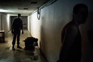 Rebels arrest a locals during a curfew