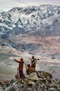 Mujahideen atop a mountain. Logar Province, 1984. The road at the bottom of the mountain links two provinces, affording these fighters the ability to see government vehicles passing below their observation point. © Steve McCurry / Magnum Photos
