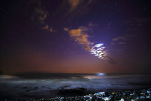 Stardust/Seascape at twilight: the Atlantic Ocean from the coast at Kommetjie, South Africa, with the moon hiding behind some clouds.