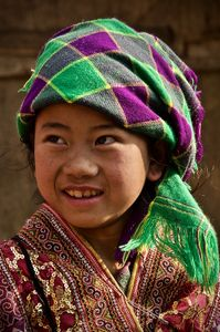 Young girl from the H'mong minority wearing a bright patterned headscarf and detailed colourful jacket.