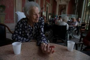 Mrs Adriana Galloni, 102 years old, seats on the porch of the retirement home Villa Cenacolo. She's a guest only on summertime for 3 months, when her own caregivers and her relatives go on vacation. She likes to stay in the porch during the afternoon chating with others guests and visitors.