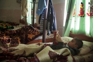 16/11/14. Alqosh, Iraq. Milad (right) reads a book in his bed in the dormitory. The children are allowed to stay in bed for longer because it is a Sunday.
