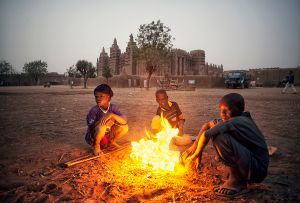 Djenné, Mali: A cold morning in front of the famous mud mosque where the children are warming up around the pile of burning rubbish. © Matjaz Krivic