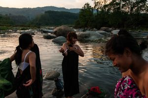 The women were given 15 minutes to wash themselves and their clothes in the river near the KIA's military base outside of Laiza, Kachin State, Myanmar, May 17, 2013. They tried to cover themselves while bathing the best that they could as the men washed just upstream.                                © Adriane Ohanesian