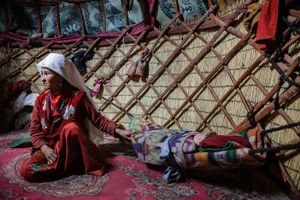 Inside a yurt in the upper Wakhan a kyrgyz woman craddle to sleep her baby.