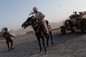 A young Afghan man selling horse rides, rides near Afghan Security Forces, in Kabul, Afghanistan on August 14, 2009. © Adam Ferguson