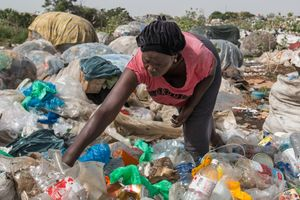 A woman is looking for plastic bottles that can be recycled. Among the waste pickers in Mbeubeuss are about 300 women and children.
