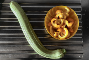 Kitchen. A courgette and some orange peels, ready to be candied.
