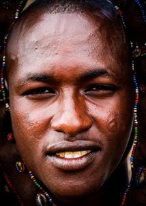 Young massai man using an ornament