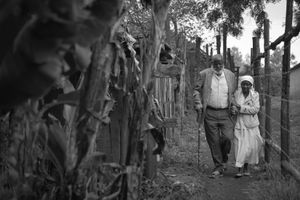 Mofat Ngwabi, an 88 year old Shona elder, is helped by his wife, Mangwenya, down a path leading to their home in the town of Kinoo on the outskirts of Nairobi, Kenya, on October 29, 2017.
