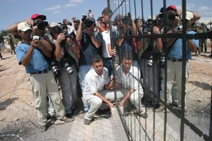 Palestinian activists places a mirror with bars in front of Israeli soldiers during a protest against the occupation in the West Bank village of Bil'in, 2005.