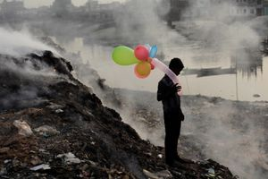 Life Along The Polluted River. A boy plays with balloons by Buriganga River as smoke emits from a dump yard during sunset in Dhaka, Bangladesh.<br> Honorable Mention People © Andrew Biraj/National Geographic Photo Contest