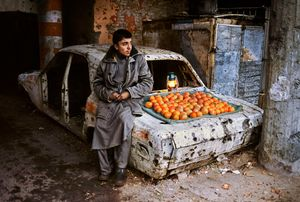 Orange Seller, Kabul, Afghanistan, 2003. This burnt-out husk of a building used to be a local police station. It is scene drained of any warmth. Yet, arranged on the ashen trunk of the car, the oranges seem to generate their own heat. With the boy's daily survival dependent on selling these meager goods, the intense color of the fruit connotes their special value.