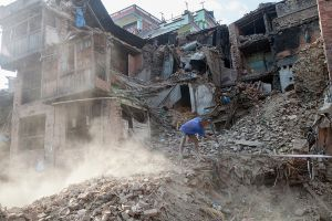 A man clears rubble and collects items from his destroyed home in Bhaktapur, Nepal.