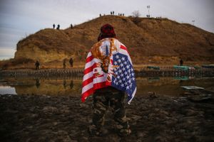 Andrew Waupekenay of the Menominee Indian Tribe of Wisconsin stands as he faces authorities on the other side of the Cantapeta Creek which runs into the Missouri River after barbed wire was placed along the shore near the Oceti Sakowin Camp on Army Corps of Engineers land bordering the Standing Rock Indian Reservation in Cannon Ball, North Dakota in November 2016.