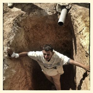A man stands in a pit designed to take waste water