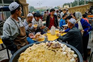 Uighurs having a dinner at the night market in old Kashgar, Xinjiang Uighur Autonomous Region, China.