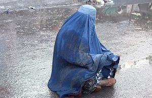 Woman wearing burqa, begging on the muddy street of Kabul, Afghanistan.