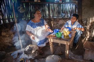 Doña Celestina Pat and her grandson Edgardo Moo Kahuil in the kitchen