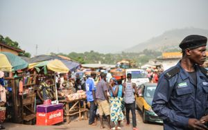 A Sierra Leone Police Officer on duty in front of a bust market place, one of the main ways of trading in the country.