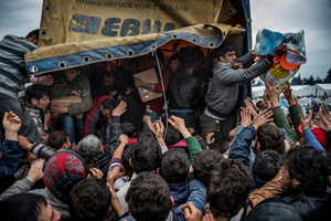 Migrants grab goods donated by volunteers in Idomeni refugees camp on the border between Greece and FYROM (Macedonia) on March 16, 2016.