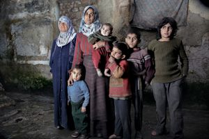 A Syrian family displaced by fighting in Aleppo stands inside the courtyard of a building where they are provided shelter by a local relief group. February 10, 2013. © Nish Nalbandian