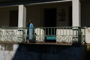 A woman standing at a front porch in Havana, Cuba