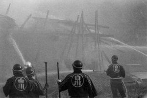 7 - I pompieri osservano il tetto e il lato sinistro ormai quasi completamente distrutti.