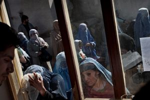 Afghan women receive food assistance at a World Food Program distribution centre in Kabul, Afghanistan on Thursday, March 8, 2011. © Adam Ferguson